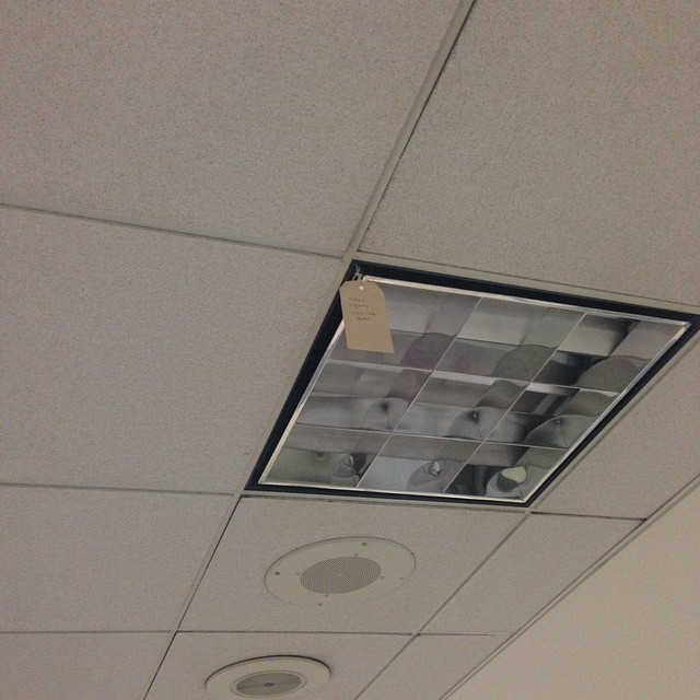 "The random tag hanging from the ceiling light randomly reads ""New lights will not burn"" @LAX"